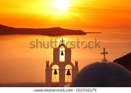 Santorini with Firostefani Church against sunset over sea, Fira, Greece - stock photo