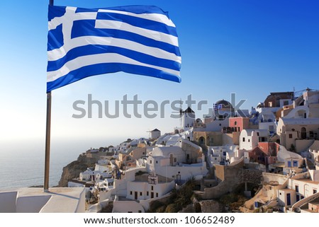 Santorini with Greek flag and windmill in Oia village - stock photo