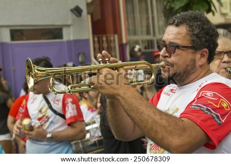 SAO PAULO, BRAZIL - JANUARY 31, 2015: An unidentified man playing trumpet in a traditional samba band participate in the annual Brazilian street carnival. - stock photo