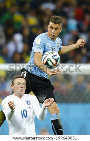 SAO PAULO, BRAZIL - June 19, 2014: Jose Gimenez of Uruguay and Wayne Rooney of England compete for the ball during the game between Uruguay and England at Arena Corinthians. No Use in Brazil. - stock photo