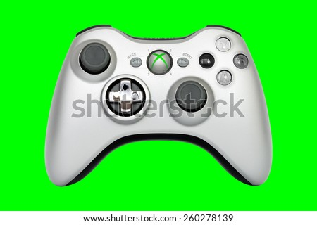 SAO PAULO, BRAZIL - MAR 13, 2014: The wireless gamepad for the Xbox 360, a home video game console produced by Microsoft, isolated on green background. - stock photo