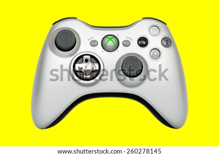SAO PAULO, BRAZIL - MAR 13, 2014: The wireless gamepad for the Xbox 360, a home video game console produced by Microsoft, isolated on yellow background. - stock photo