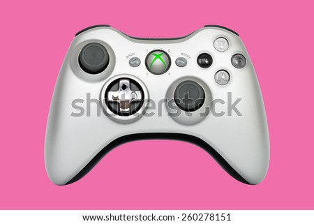 SAO PAULO, BRAZIL - MAR 13, 2014: The wireless gamepad for the Xbox 360, a home video game console produced by Microsoft, isolated on pink background. - stock photo