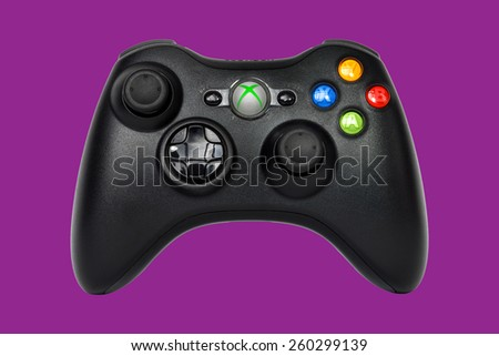 SAO PAULO, BRAZIL - MAR 13, 2014: The wireless gamepad for the Xbox 360, a home video game console produced by Microsoft, isolated on purple background. - stock photo