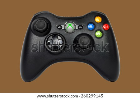 SAO PAULO, BRAZIL - MAR 13, 2014: The wireless gamepad for the Xbox 360, a home video game console produced by Microsoft, isolated on brown background. - stock photo