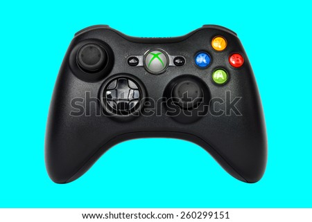 SAO PAULO, BRAZIL - MAR 13, 2014: The wireless gamepad for the Xbox 360, a home video game console produced by Microsoft, isolated on emerald blue background. - stock photo