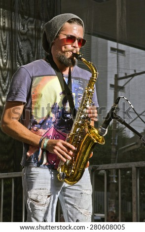 SAO PAULO, BRAZIL - MAY 17, 2015: An unidentified musician  playing saxophone on the street in Sao Paulo, Brazil.  - stock photo
