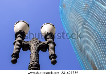 SAO PAULO, BRAZIL - NOVEMBER 18, 2014: Detail of Facade renovation of the Copan building and old pole light in downtown Sao Paulo. Copan is the largest residential building in the world. - stock photo