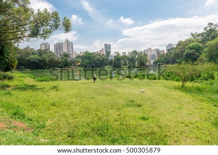 Sao Paulo, Brazil - October 15 2016: People enjoying their leisure free time to walk together with their dog at the Aclimacao Park. which was founded by Carlos Botelho, Brazil.