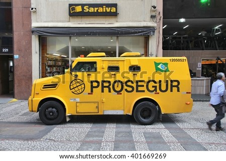 SAO PAULO, BRAZIL - OCTOBER 6, 2014: People pick up money from store in armored vehicle in Sao Paulo, Brazil. Robberies and other violent crimes are frequent in Brazil. - stock photo