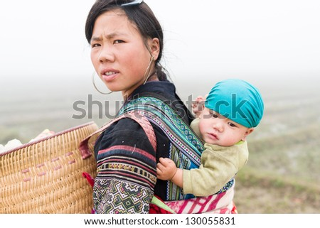 SAPA, VIETNAM - DEC 04: Unidentified H'mong woman and child in Sa Pa, Vietnam December 04, 2012. Sapa is a mountain town in Vietnam and H'mong are the 8th largest ethnic group in Vietnam. - stock photo