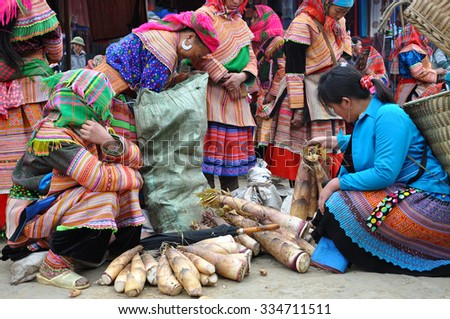SAPA, VIETNAM - FEBRUARY 22, 2013: Hmong women at Bac Ha market in Northern Vietnam. Bac Ha is hilltribe market where people come to trade for goods in traditional costumes - stock photo