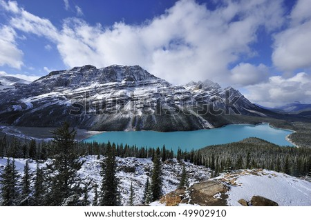 Sapphire-blue of star-shaped Peyto Lake blinking white-grey snowy mountains rimmed with white clouds Banff - stock photo