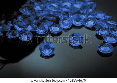 Sapphires scattered on a shiny surface with prominent sapphire in the middle