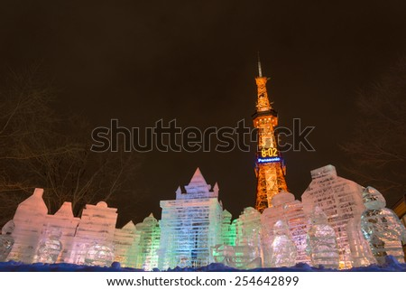 SAPPORO, JAPAN - FEB. 6 : Illuminated ice sculpture of an imaginary castle and Sapporo TV Tower at Sapporo Snow Festival on February 6, 2015 in Sapporo, Hokkaido, japan. - stock photo