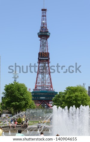 SAPPORO, JAPAN - JUNE. 1 : Sapporo TV Tower and the West 3 Fountain on June 1, 2013 in Sapporo, Hokkaido, japan. The Tower and Fountain are located at Sapporo Odori Park. - stock photo