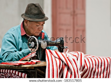 SAQUISILI, ECUADOR - AUGUST 18: A street tailor is making a traditional striped poncho with his old Singer sewing machine on August 18, 2012 in Saquisili, Ecuador - stock photo