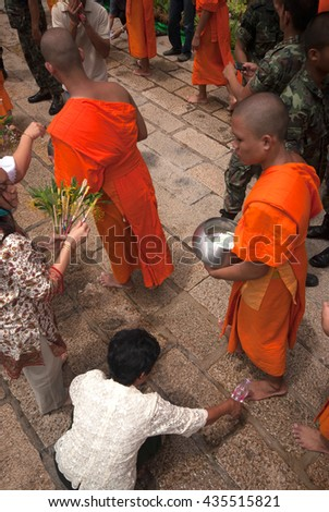 SARABURI,THAILAND -JULY 7, 2009 : Group of monks receiving flower offering from people in Tak Bat Dok Mai or Flower Offering Ceremony at Phrabuddhabat Woramahavihan Temple , Saraburi ,Thailand. - stock photo