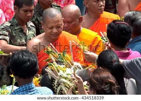 SARABURIi,THAILAND-JULY 7,2009 : Unidentified People Give Flowers to Buddhist Monks for alms in The Tak Bat Dok Mai (give flowers to monk) Ceremony at Phrabuddhabat Woramahavihan in Saraburi,Thailand. - stock photo