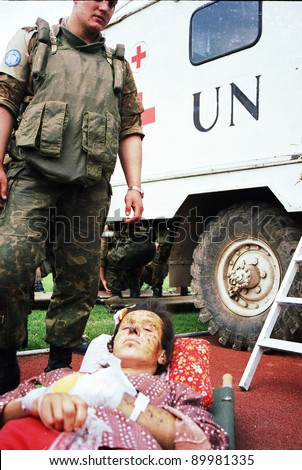 SARAJEVO, BOSNIA - APR 4: A Ukrainian soldier, in Bosnia with United Nations Protection Force (UNPROFOR),  watches over a Bosnian woman wounded in Gorazde in a medical facility in Sarajevo, Bosnia, on Monday,  April 4, 1994. - stock photo