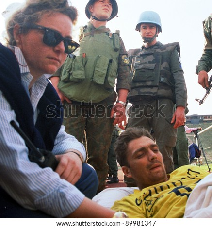 SARAJEVO, BOSNIA - APR 4: An aid worker, along with United Nations Protection Force (UNPROFOR)  comforts a Bosnian man wounded during the siege of Gorazde in amedivac facility in Sarajevo, Bosnia, on Monday,  April 4, 1994. - stock photo