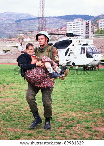 SARAJEVO, BOSNIA - APR 4: An Ukrainian soldier with the United Nations Protection Force (UNPROFOR) in Bosnia carries a woman wounded during the siege of Gorazde at a medical center in Sarajevo, Bosnia, on Monday, April 4, 1994 - stock photo