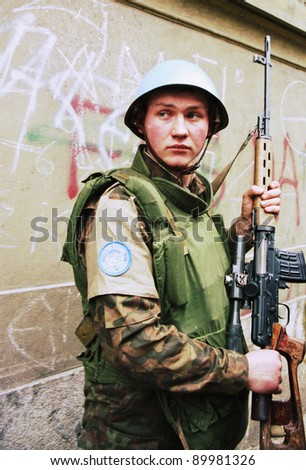 SARAJEVO, BOSNIA - FEB 16: A Ukrainian peacekeeper with the United Nations Protection Force (UNPROFOR), stands guard during an evacuation of refugees from Sarajevo, Bosnia, on Tuesday, February 16, 1993. - stock photo