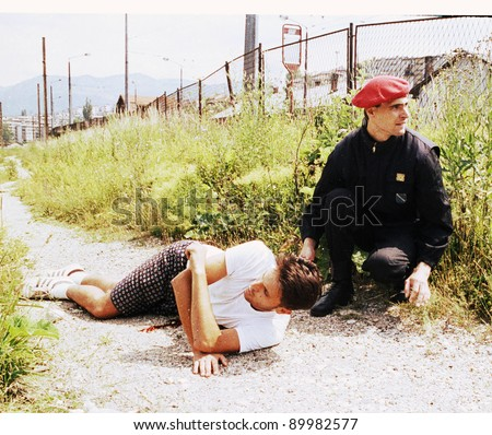 SARAJEVO, BOSNIA - JUNE 17: A soldier comes to the aid of a man critically injured by a sniper's bullet in a train yard in Sarajevo, Bosnia, on Thursday, June 17, 1993. - stock photo