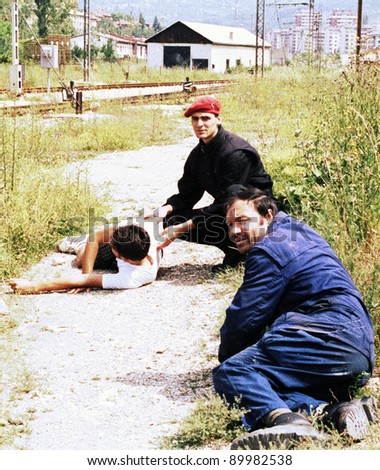 SARAJEVO, BOSNIA - JUNE 17: Two men duck for cover while trying to help another man critically injured by a sniper's bullet in a train yard in Sarajevo, Bosnia, on Thursday, June 17, 1993. - stock photo