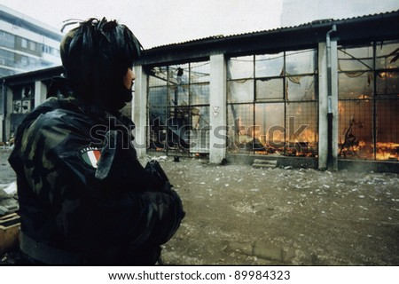 SARAJEVO, BOSNIA - MAR 18: Italian army troops, in Bosnia as part of the United Nations' UNPROFOR, patrol a burning outdoor market in Sarajevo, Bosnia, on Monday, March 18, 1996. - stock photo