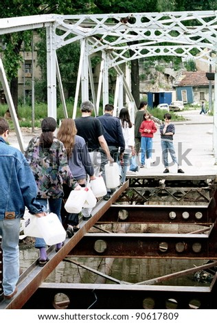 SARAJEVO, BOSNIA - SEP 15: Sarajevans cross a destroyed bridge in the besieged capital of Bosnia on their way to find water in Sarajevo, Bosnia, on Sunday, SEPT 15, 1993. - stock photo