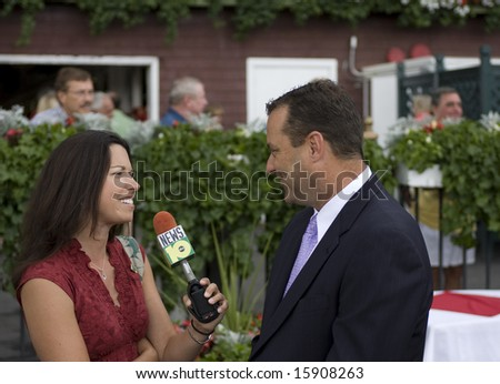 SARATOGA SPRINGS - August 7: Kentucky University Basketball Coach Billy Gilliespie intervied by ABC Reporter Jamie Seh in the Winners Circle after 4th race August 7, 2008 in Saratoga Springs, NY - stock photo