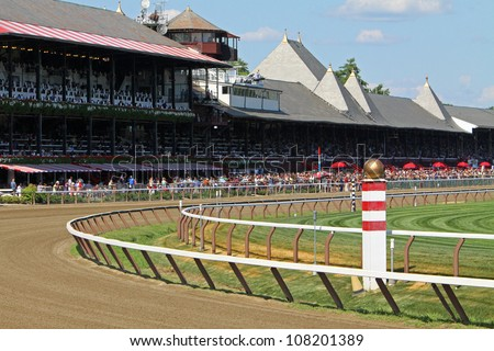 SARATOGA SPRINGS - JUL 21: Fans crowd historic Saratoga Race Course on Coaching Club American Oaks Day on Jul 21, 2012 in Saratoga Springs, NY. - stock photo