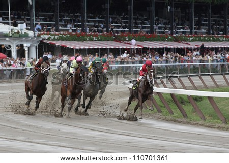 SARATOGA SPRINGS, NY - JULY 27: The field moves through the clubhouse turn in the fifth race on July 27, 2012 at Saratoga Springs, New York - stock photo
