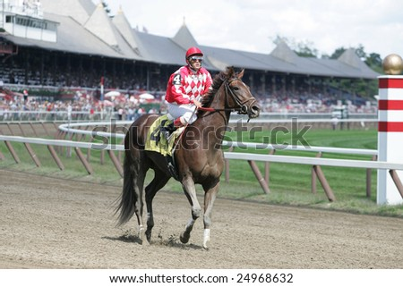SARATOGA SPRINGS - September 4: Unknown jockey rides out his mount after the finishes of the third race on September 4, 2005 in Saratoga Springs, NY. - stock photo