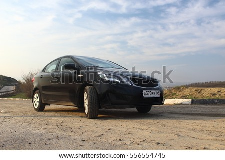 Saratov, Russia - April 15, 2016: Motor car black Kia Rio in the country. Spring season. This model is called in China Kia k2.