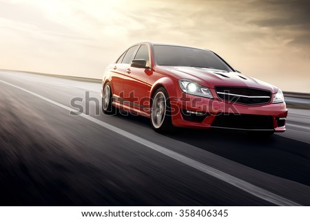 Saratov, Russia - August 24, 2014: Red sportcar Mercedes-Benz C63 AMG fast speed driving on the asphalt road at daytime - stock photo
