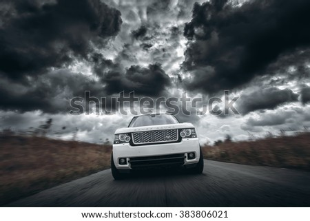 Saratov, Russia - October 11, 2015: White car Land Rover Range Rover speed driving on road at dramatic clouds daytime