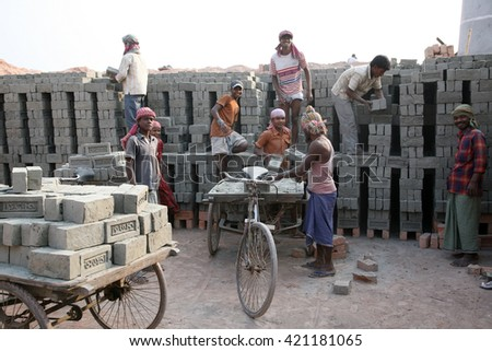 SARBERIA,INDIA, JANUARY 16: Brick field workers carrying complete finish brick from the kiln, and loaded it onto a bicycle rickshaw on January 16, 2009 in Sarberia, West Bengal, India. - stock photo