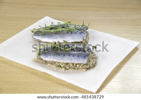 sardines fish with breadcrumbs, lemon and thymes on wooden background