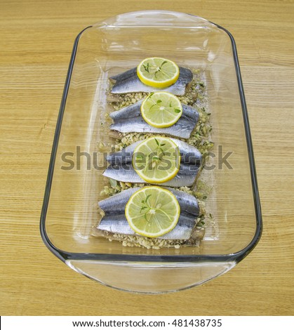 sardines fish with breadcrumbs, lemon and thymes on wooden background, Stuffed baked sardines.