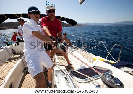 "SARONIC GULF, GREECE - SEPTEMBER 25: Unidentified sailor participates during of sailing regatta ""Viva Greece 2012"" on September 25, 2012 on Saronic Gulf, Greece. - stock photo"
