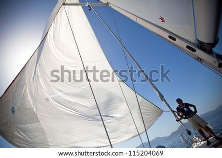 "SARONIC GULF, GREECE - SEPTEMBER 26: Unidentified sailor participates in sailing regatta ""Viva Greece 2012"" on September 26, 2012 on Saronic Gulf, Greece. - stock photo"
