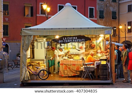 SARZANA, ITALY - AUGUST 10, 2015: View inside the open tent on the square - Piazza Giacomo Matteotti in Sarzana, Italy. Summer local food festival. - stock photo