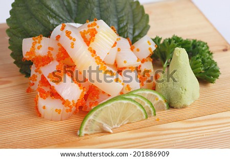 Sashimi , a Japanese delicacy consisting of very fresh raw meat or seafood sliced into thin pieces, seafood in this photo is squid and salmon eggs - stock photo