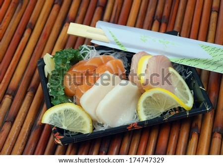 Sashimi Takeout.  Fresh salmon, yellowtail snapper and white tuna sashimi in a takeout tray on bamboo mat.