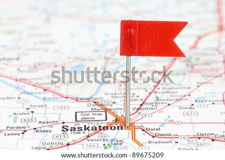 Saskatoon in Saskatchewan, Canada. Red flag pin on an old map showing travel destination. - stock photo