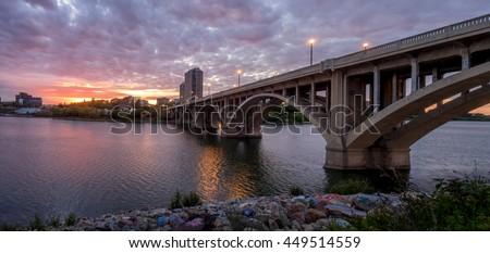 Saskatoon skyline at night along the Saskatchewan River.  - stock photo