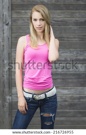 Sassy and young girl posing in casual teen outfit of white belt and ripped denim pants and pink top - stock photo