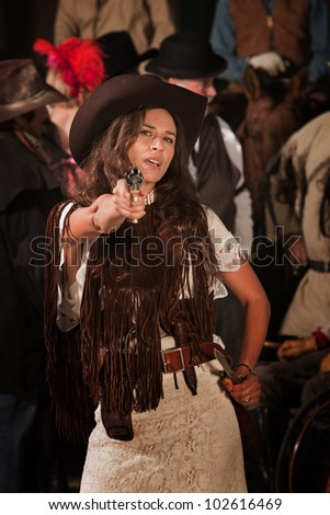 Sassy Latina woman in western outfit with pistol and dagger - stock photo
